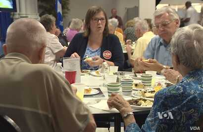 Democrat Emily Cain, a former Maine state senator and now a candidate for the U.S. House of Representatives, meets with prospective voters over lunch at the Franco-American Center in Lewiston, Maine.