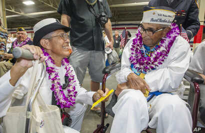 Kathleen Chavez, left, talks with her father Ray Chavez, right, age 104, of the USS Condor the oldest living survivor from the Pearl Harbor attacks along with the remaining living survivors of the USS Arizona gathered at the World War II Valor in the...