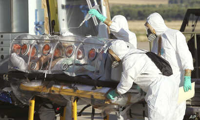 In this photo provided by the Spanish Defense Ministry, aid workers and doctors transfer Miguel Pajares, a Spanish priest who was infected with the Ebola virus while working in Liberia, from a plane to an ambulance as he leaves the Torrejon de Ardoz ...