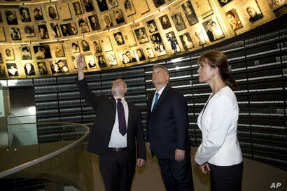 Hungarian Prime Minister Viktor Orban, center, and this wife Aniko Levai visit the Hall of Names at the Yad Vashem Holocaust Memorial in Jerusalem, July 19, 2018.