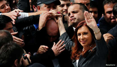 Former Argentine President Cristina Fernandez de Kirchner waves to supporters as she leaves a Justice building where she attended court to answer questions over a probe into the sale of U.S. dollar futures contracts at below-market rates by the centr...