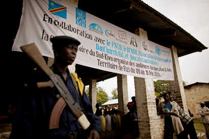 FILE - A Congolese soldier stands guard outside a military tribunal in Baraka, Democratic Republic of Congo, Feb. 17, 2011. Eleven soldiers were charged with crimes against humanity over an instance of mass rape and looting in the eastern town of Fiz...