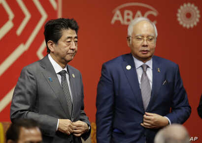 Japan's Prime Minister Shinzo Abe (left) and Malaysia's Prime Minister Najib Razak leave after a meeting between leaders of the Asia Pacific Economic Cooperation, APEC, and regional business leaders, in Lima, Peru, Nov. 19, 2016.