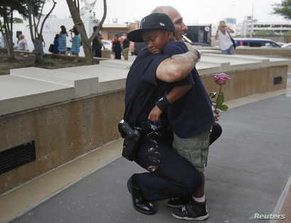 A Dallas Police officer hugs a child who came to pay respects at a makeshift memorial at Dallas Police Headquarters following the multiple police shootings in Dallas, Texas, U.S., July 9, 2016.