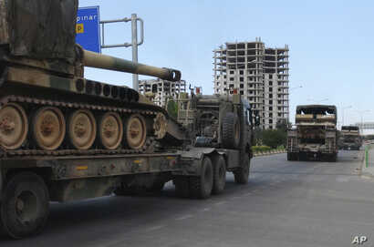 FILE - A convoy of Turkish military trucks carrying tanks destined for Syria, moves near the town of Kilis, Turkey,Sept. 14, 2018.