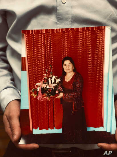 Ferkat Jawdat holds up a photo of his mother during a gathering to raise awareness about loved ones who have disappeared in China's far west, in Washington D.C., Feb. 24, 2019.