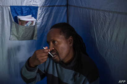 45-year-old Oscar Tyumre uses an HIV self-testing kit, administered by students from the University of the Witwatersrand in Hillbrow, Johannesburg, on March 19, 2018. Self-testing kits and vending machines distributing prescription drugs are two ways...