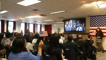 """A hundred immigrants, from 31 countries, join in singing """"America, the Beautiful"""" after becoming naturalized U.S. citizens. (M. Cuevas/VOA)"""