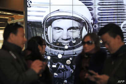 Tourists gather near a tribute to former astronaut and U.S. Senator John Glenn, at the National Air and Space Museum, Dec. 9, 2016 in Washington, D.C.