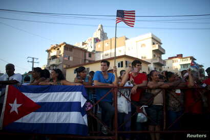 A man holds a U.S. flag while gathering with others on a sidewalk near the U.S. embassy (not pictured) in Havana, Cuba, Aug. 14, 2015.