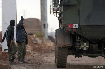 Turkish military vehicles drive by Free Syrian Army fighters, backed by Turkey, in the Syrian rebel-held town of al-Rai as they head towards the northern Syrian town of al-Bab, Jan. 9, 2017.