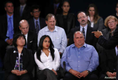Members of the audience look on as U.S. President Barack Obama (R) speaks as he debates Republican presidential nominee Mitt Romney during the second U.S. presidential debate in Hempstead, New York October 16, 2012.