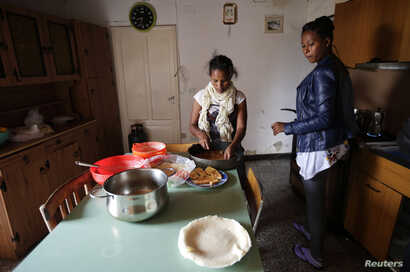 FILE - Eritrean migrants prepare food in their home in Riace, Calabria region, Italy, Nov. 21, 2013.