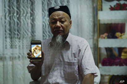 Ablikim Abliz holds up his phone with a photo of his uncle's family with an unknown Han Chinese man in Istanbul, Turkey, Aug. 22, 2018. He later heard that his uncle's front door was boarded up and sealed with police tape, and has not been able to co...