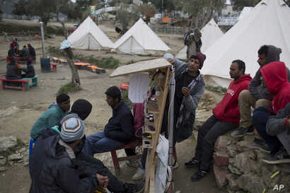 Pakistani men charge their mobile phones in a makeshift migrant camp made by volunteers near the village of Moria, Lesbos island , Greece, March 22, 2016.
