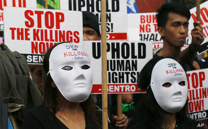 Masked protesters gather for a rally near the Presidential Palace to mark International Human Rights Day, Dec. 10, 2016, in Manila, Philippines. The protesters are calling on the government for an end to extrajudicial killings in the country, which h
