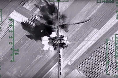 FILE - In this photo made from the footage taken from Russian Defense Ministry official web site on Feb. 1, 2016,  an aerial image shows what it says is a column of heavy trucks carrying ammunition hit by a Russian air strike near Aleppo, Syria.