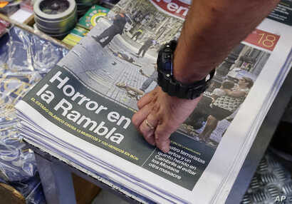 A newspaper displays a photograph of the aftermath of the terror attack in Las Ramblas, in Barcelona, Spain, Aug. 18, 2017. A white van jumped onto a sidewalk and sped down a pedestrian zone Thursday in Barcelona's historic Las Ramblas district, swer...