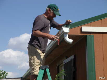 Jack Rose installs a gutter on the White Plume home. (VOA/J. Kent)
