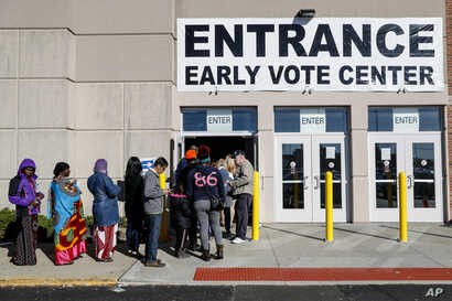 A line of early voters waits outside the Franklin County Board of Elections, Monday, Nov. 7, 2016, in Columbus, Ohio. Heavy turnout has caused long lines as voters take advantage of their opportunity to vote before election day.