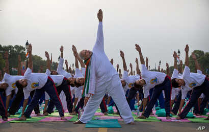Prime Minister Narendra Modi performs yoga along with thousands of Indians on Rajpath in New Delhi, India, June 21, 2015.