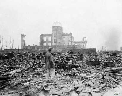 FILE - In this Sept. 8, 1945 file photo, an allied correspondent stands in the rubble in front of the shell of a building that once was a movie theater in Hiroshima, Japan, a month after the first atomic bomb ever used in warfare was dropped by the U...