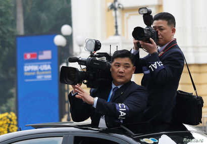 Members of North Korean media take images as the motorcade of North Korea's leader Kim Jong Un rides past the Opera House, after the second U.S.-North Korea summit in Hanoi, Vietnam, Feb. 28, 2019.