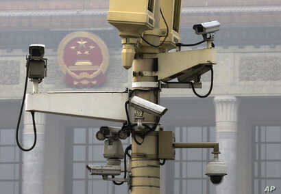 A pole attached with security cameras to monitor Tiananmen Square stands against a backdrop of the Chinese Communist Party emblem on the Great Hall of the People shrouded by thick haze in Beijing, Oct. 20, 2014.