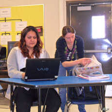 Nicky Oulette reviews the current issue of the Mustang News while Madeline Buckman works on her column.