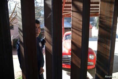 FILE - A man in Nogales, Sonora, Mexico looks through the U.S. border fence into Nogales, Arizona, U.S., January 31, 2017.