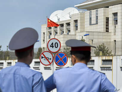 FILE - Kyrgyz police officers look at the Chinese Embassy after a suicide bombing in Bishkek, Kyrgyzstan, Aug. 30, 2016. In the past two years, militants belonging to the Uighur ethnic group native to the vast Xinjiang region in western China have sh...