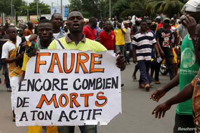 """FILE - A man holds up a sign, which reads: """"Faure still how many death by you,"""" during an opposition protest calling for the immediate resignation of President Faure Gnassingbe in Lome, Togo, Sept. 6, 2017."""