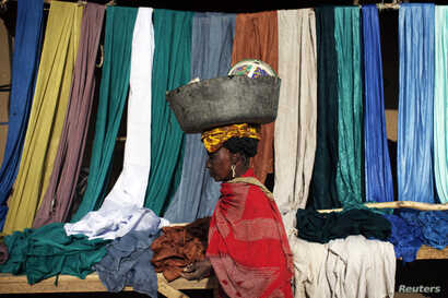 A woman carries a bucket on her head as she walks past fabrics for sale in Gao, Mali, Feb. 2013.