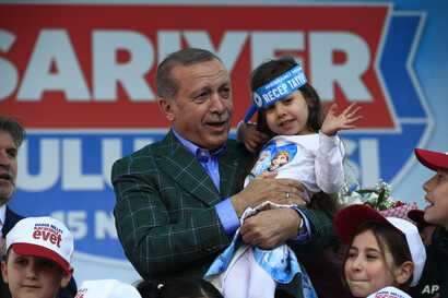 Turkey's President Recep Tayyip Erdogan holds a young girl during his last rally ahead of Sunday's referendum, in Istanbul, April 15, 2017.