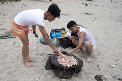 North Korean men prepare to barbecue duck meat on the seashore near Mount Chilbo, North Korea.