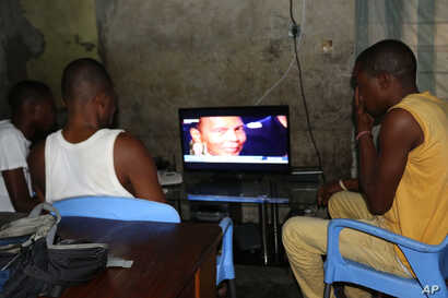 People in Kinshasa, D.R.C., look at a program reporting on the death of former heavyweight boxing champion Muhammad Ali, June 4, 2016.