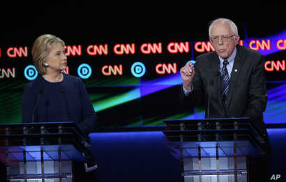 Democratic presidential candidate, Sen. Bernie Sanders, I-Vt., right, argues a point as Hillary Clinton listens during a Democratic presidential primary debate at the University of Michigan-Flint, Sunday, March 6, 2016, in Flint, Michigan.