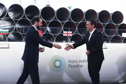 Greece's Prime Minister Alexis Tsipras, right, shake hands with Turkish Minister of Energy Berat Albayrak during the Trans Adriatic Pipeline inauguration ceremony, in the northern Greek city of Thessaloniki, May 17, 2016.