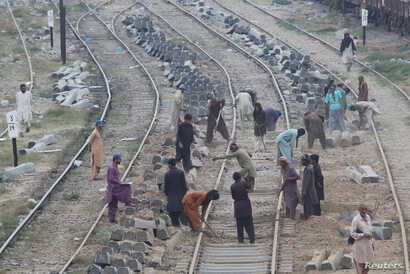 Laborers dig the ground before replacing concrete sleepers along railway tracks in Karachi, Pakistan, Jan. 11, 2018.