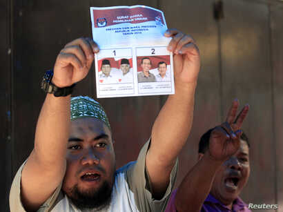 An election official holds up a ballot paper during the counting of votes cast in the country's presidential election, in Makassar, South Sulawesi, Indonesia, July 9, 2014.
