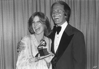 FILE - Debby Boone holds her Grammy award for best new artist as she gets a hug from her father, singer Pat Boone, at the Grammy Awards in Los Angeles, Feb. 21, 1978.