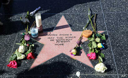 An impromptu memorial created on a blank Hollywood Walk of Fame star by fans of the late actress and author Carrie Fisher, who does not have an official star on the world-famous promenade, is seen in Los Angeles, Dec. 28, 2016. Paste-on letters spell...