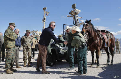 Acting Secretary of Defense Patrick Shanahan, center, greets Border Patrol Agents Carlos Lerma, second from right, Moises Gonzalez, right, and the horse they use for patrols during a tour of the U.S.-Mexico border at Santa Teresa Station in Sunland P...