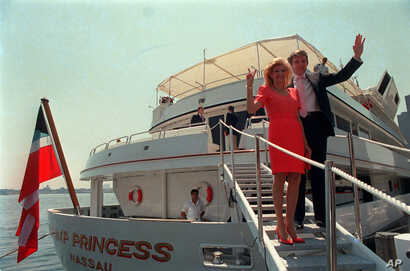 Real estate developer Donald Trump waves to reporters with his wife, Ivana, as they board their luxury yacht The Trump Princess in New York City on Monday, July 4, 1988.  Trump paid the Sultan of Brunei $30 million for the nearly 300-foot yacht.  (AP...