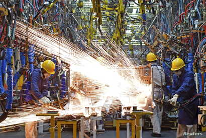 Employees work along a production line at a factory of Dongfeng Nissan Passenger Vehicle Co. in Zhengzhou, Henan province, China, Nov. 12, 2015.