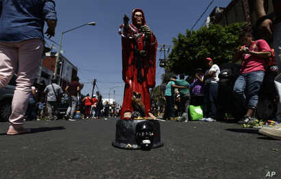 "In this March 1, 2017 photo, a Death Saint or ""Santa Muerte"" statuette stands in the middle of the road, placed there by its owner who waits for people to offer it things like food, tobacco and alcohol, in Mexico City's Tepito neighborhood."