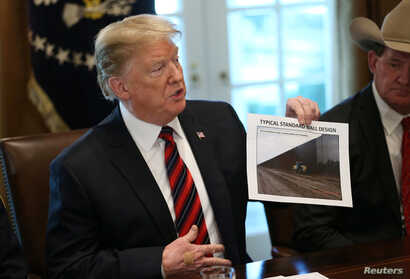 "U.S. President Donald Trump holds up a photo of a ""Typical Standard Wall Design"" as he hosts a ""roundtable discussion on border security and safe communities"" with state, local, and community leaders in the Cabinet Room of the White House in Washingt..."
