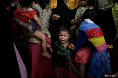 A baby cries as Rohingya refugees line up for a food supply distribution at the Kutupalong refugee camp near Cox's Bazar, Bangladesh Dec. 12, 2017.