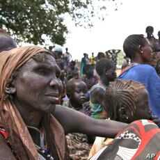 People wait at the food distribution center set up by the World Food Program in Gumuruk, 40 kilometers from Pibor, South Sudan, January 17, 2012.