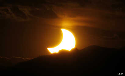 FILE - The annular solar eclipse is seen as the sun sets behind the Rocky Mountains from downtown Denver, Colorado, May 20, 2012.